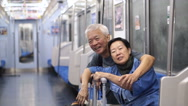 Asian Senior using public transportation to do retirement travel trip Stock Footage