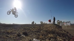 Silhouette of men racing motorcycles in a motocross motor sports race. Stock Footage