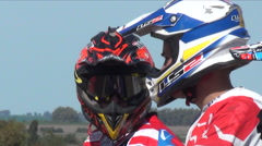 Close-up of men wearing their helmets before racing in a motocross motor sports Stock Footage