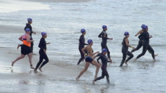 Athletes compete at the start of a triathlon by running into the surf. Stock Footage