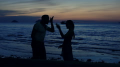 Silhouette of couple fighting, arguing on beach during sunset Stock Footage