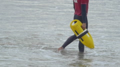 A lifeguard with his yellow rescue can and swim fins. Stock Footage