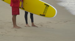 Lifeguards talk on the beach with a rescue can and paddleboard. Stock Footage