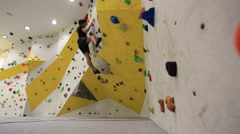 Wide shot of a young man who climbs in an indoor climbing gym. Stock Footage