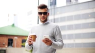 Man with smartphone and coffee cup on city street Stock Footage