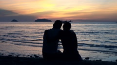 Silhouette of couple hugging and admire sunset on beach Stock Footage