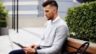 Man with tablet pc sitting on city street bench Stock Footage
