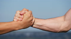 Two strong men having firm handshake outside. Teamwork and friendship. Close-up Stock Footage