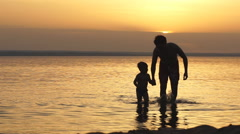 Father and Son Holding Hands Walking Together on the Beach at Sunset Stock Footage