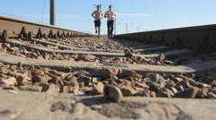 Sprinting runner guys jogging on railway sleepers. Legs of sport athletes Stock Footage
