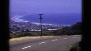 1953: sky, sea and land meet in curved and crowded coastal town below road Stock Footage