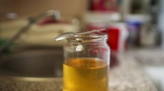The honey jar at the kitchen table. Spoonful of honey Stock Footage