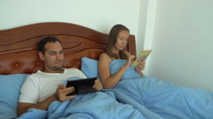 Young couple using their tablets in bed ignoring each other. Family issues Stock Footage