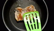 Cook turns grilled meat on a frying pan using a cooking spatula. Top view. Stock Footage