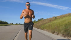Young smiling muscular man in sun glasses jogging at highway Stock Footage