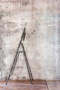 Old concrete wall in repairing room with dirty brown floor and stepladder Stock Photos