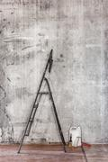 Old concrete wall in repairing room with dirty floor,tools and stepladder Stock Photos