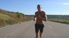 Young strong muscular guy exercising on rural road during workout. Lifestyle Stock Footage