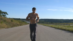 Sprinting runner man jogging at highway. Male sport athlete training outdoor Stock Footage