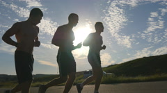 Silhouette of strong men jogging in the country road at sunset time. Stock Footage