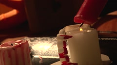 Rack focus melting red wax on white candle, vampire teeth Stock Footage