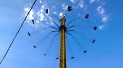 People spinning on the merry-go-round in amusement park high above the ground on Stock Footage