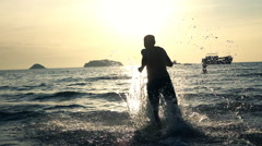 Silhouette of man running in sea during sunset, super slow motion 240fps Stock Footage