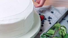 Girls is decorating cake with blueberry, close up Stock Footage