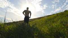 Young man running over green hill over blue sky background. Stock Footage