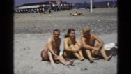 1953: two men and woman sitting on the beach and talking CALIFORNIA Stock Footage