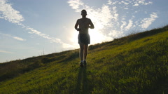 Young man running over green hill over blue sky background. Athlete is jogging Stock Footage