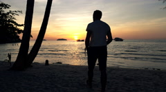 Silhouette of man walking on beach and admire sunset  Stock Footage