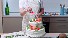Girl decorates tier cake with fresh green, peach, blueberry and cherry Stock Footage