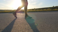 Legs of young boy move along the pathway. Guy crossing a sunlit route. Stock Footage