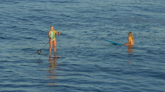 A young woman SUP surfing in a bikini on a stand-up paddleboard surfboard. Stock Footage