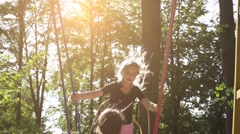 Slow Motion: Two sisters ride on swing Stock Footage