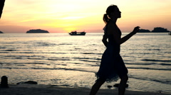 Silhouette of woman running on beach during sunset, super slow motion 240fps Stock Footage