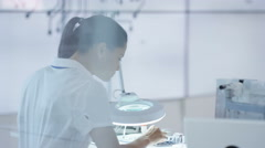 4K Electronic engineer working in lab looking at motherboard under magnifier Stock Footage