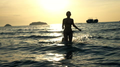Silhouette of woman running in sea during sunset, super slow motion 240fps Stock Footage