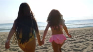 Two little girls running on the sea beach Stock Footage