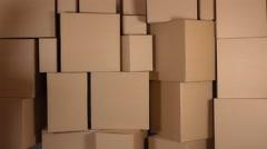 Slender girl in orange uniform delivering a parcel against carton stacks Stock Footage