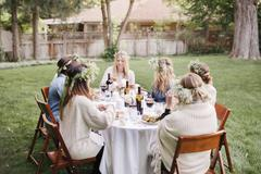 Group of female friends gathered around a table ingarden eating and drinking Stock Photos