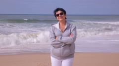Attractive active mature woman standing on an ocean beach and smiling at camera. Stock Footage