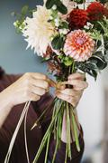Organic flower arrangements A woman creating a hand tied bouquet Stock Photos