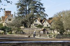 Walled vegetable garden with mature trees and view to historic house Stock Photos
