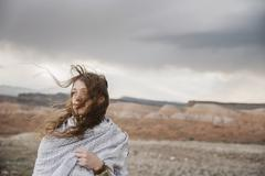 A woman with long hair blowing in the wind standing indesert landscape Stock Photos