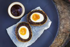 Blue dish with a fresh made scotch egg cut in to two Stock Photos