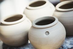 Four small round pots with round openings vases of fresh turned clay Stock Photos