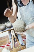 A potter handling a ball of wet clay pot moulding and working it Stock Photos