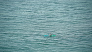 A small green paddle boat in the ocean Stock Footage